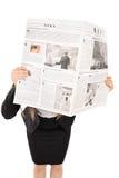 Studio van een vrouw wordt geschoten die achter een krant verbergen die Stock Fotografie