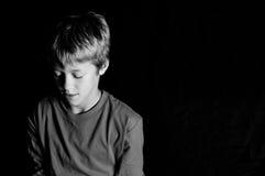 Studio van jonge jongen op zwarte achtergrond wordt geschoten die royalty-vrije stock afbeeldingen