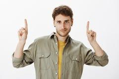 Studio van knappe krullend-haired kerel met baard wordt, die over grijze achtergrond met opgeheven wijsvingers stellen, het richt royalty-vrije stock afbeeldingen