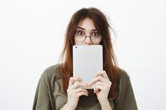 Studio van schuchtere grappige vrouw met slordig haar in glazen wordt geschoten, die de helft van gezicht met digitale tablet, ge royalty-vrije stock afbeeldingen