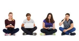 Studio van Tieners wordt geschoten die Communicatietechnologie gebruiken die Stock Foto's