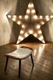 Studio verziert mit L hölzerner Stern mit Glühlampen lizenzfreies stockbild