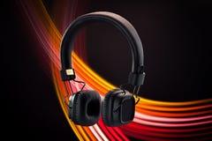 Studio wireless headphones on a black background. Beautiful black professional studio wireless headphones on a black background with fiery red decorative stripes stock photos