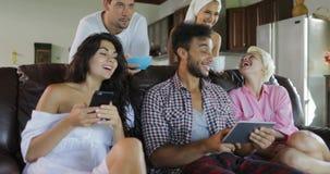 Studio-Wohnungs-Unterhaltungsgebrauchs-Tablet-Computer junge Leute-Gruppen-Morgen-Uhr Fernsehen Sit On Coach In Modern stock video