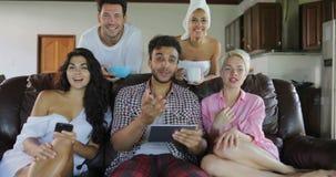 Studio-Wohnungs-Unterhaltungsgebrauchs-Tablet-Computer junge Leute-Gruppen-Morgen-Uhr Fernsehen Sit On Coach In Modern stock footage
