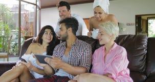 Studio-Wohnungs-Unterhaltungsgebrauchs-Tablet-Computer junge Leute-Gruppen-Morgen-Uhr Fernsehen Sit On Coach In Modern stock video footage