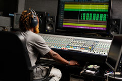 Studio work. Sound producer sitting by mixing equipment in studio royalty free stock images
