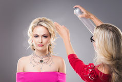 Studio worker applying a hair spray over beautiful blonde's hair wearing pink dress and necklace Royalty Free Stock Photo