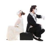 Studioabbildung von zwei Pantomimen, die auf Koffer sitzen Lizenzfreie Stockfotografie