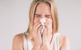 Studiobild från en ung kvinna med näsduken Den isolerade sjuka flickan har den rinnande näsan Den kvinnliga modellen gör en bot f royaltyfria bilder