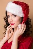 Studiocloseupstående av en härlig flicka i hatten av Santa Claus, Fotografering för Bildbyråer