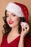 Studiocloseupstående av en härlig flicka i hatten av Santa Claus, Arkivbild