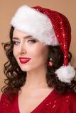 Studiocloseupstående av en härlig flicka i hatten av Santa Claus, Royaltyfria Foton