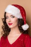 Studiocloseupstående av en härlig flicka i hatten av Santa Claus, Royaltyfri Fotografi