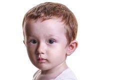 Studiocloseupståenden av lite behandla som ett barn pojken med den allvarliga framsidalooen Arkivfoton