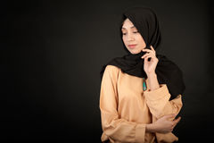 Studiofoto av en härlig östlig typ för ung kvinna som är hellång, på en mörk bakgrund som är iklädd den muslimska stilen Arkivfoto