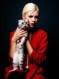 Studiofoto der jungen Frau mit Katze auf schwarzem Hintergrund Stockfoto