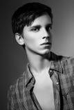 Studiofoto des jungen Mannes auf grauem Hintergrund Stockbild