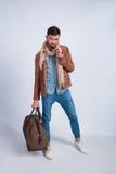 Studiofoto des jungen Mannes mit einer Reisetasche stockbild