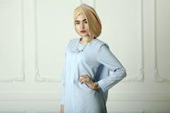 Studiofoto van een jong vrouwen oostelijk type in de moderne Moslimkleren, het mooie hoofddeksel en een gouden horloge royalty-vrije stock foto