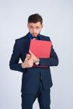 Studiofotogeschäftsmann mit rotem Ordner Lizenzfreie Stockbilder