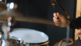 Studiomens van band in het zwarte moderne sweatshot spelen op de trommels en drum-type platen stock videobeelden