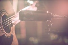 Studiomikrofonen antecknar en närbild för akustisk gitarr Härlig suddig bakgrund av kulöra lyktor royaltyfri fotografi