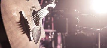 Studiomikrofonen antecknar en närbild för akustisk gitarr Härlig suddig bakgrund av kulöra lyktor royaltyfria foton