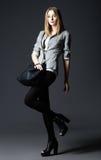 Studiomode geschossen: schöne junge Frau in den Gamaschen und in der Jacke, mit Tasche Stockfoto