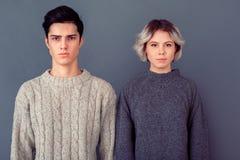 Studion för den unga mannen och kvinnaskjuter på den allvarliga gråa väggen royaltyfri bild