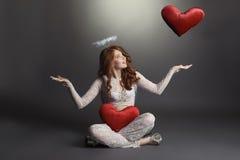 Studion sköt av den kvinnliga ängeln som spelar med hjärtor Royaltyfri Foto