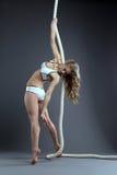 Studion sköt av den sexiga flickan som poserar att hänga på rep Arkivfoto