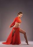 Studion sköt av en härlig sportig kvinna i röda kläder Arkivfoto