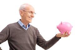 Studion sköt av en pensionär som ler på en piggybank Fotografering för Bildbyråer