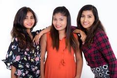 Studion sköt av tre lyckliga unga persiska kvinnavänner som ler w Arkivbilder