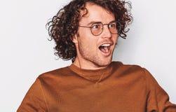 Studionahaufnahmeporträt des aufgeregten erfolgreichen männlichen Studenten oder des Angestellten mit dem gelockten Haar schreien stockfotografie