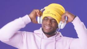 Studioporträt des hübschen jungen Mannes der afrikanischen Ewigkeit und der Kopfhörer stock video