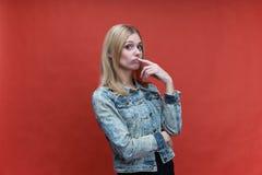 Studioporträt auf rotem Hintergrundmädchenjugendlichem mit dem langen Haar und einem Anstarren verwies an der Kamera lizenzfreies stockbild