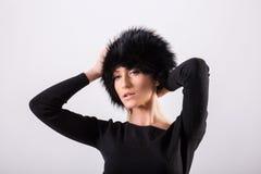 Studioporträt der blonden Frau der Schönheit, die in der schwarzen Kleidung und im schwarzen Pelzhut steht Stockbild