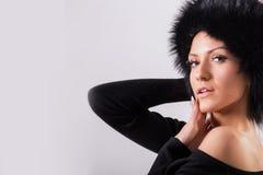 Studioporträt der blonden Frau der Schönheit, die in der schwarzen Kleidung und im schwarzen Pelzhut steht Stockfotografie