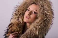 Studioporträt der blonden Frau der Schönheit, die in der schwarzen Kleidung und in der schwarzen Lederjacke mit Pelzkragen steht Lizenzfreie Stockfotos