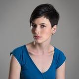 Studioporträt der ernsten misstrauischen jungen Frau mit Ausfragenblick auf Kamera Lizenzfreie Stockfotos