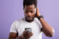 Studioporträt des amerikanischen Mannes aufwerfend mit Smartphone lizenzfreie stockfotografie