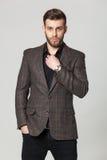 Studioporträt des hübschen eleganten jungen Mannes in der braunen Jacke PO stockfoto