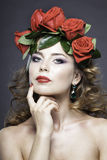 Studioporträt des hübschen Mädchens mit roten Rosen Stockfotografie