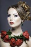 Studioporträt des hübschen Mädchens mit roten Rosen Stockfoto