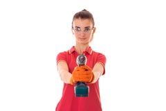 Studioporträt des jungen schönen Brunettemädchens in der Uniform und in den Gläsern lässt renavation mit die Hände herein bohren, lizenzfreies stockbild