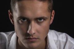 Nahaufnahmeporträt des ernsten und schönen jungen Mannes Stockbilder