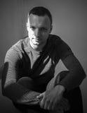 Studioporträt des Sitzens des jungen erwachsenen Mannes Lizenzfreies Stockfoto