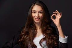 Studioporträt einer attraktiven Frau, die das OKAYzeichen zur Kamera gibt Stockfotografie